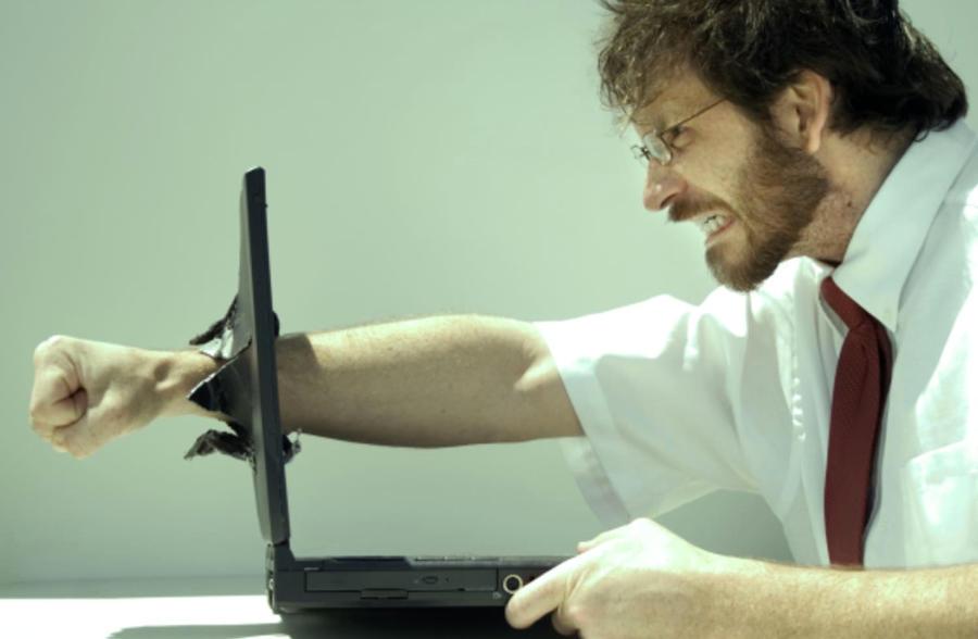 man punching through a laptop screen