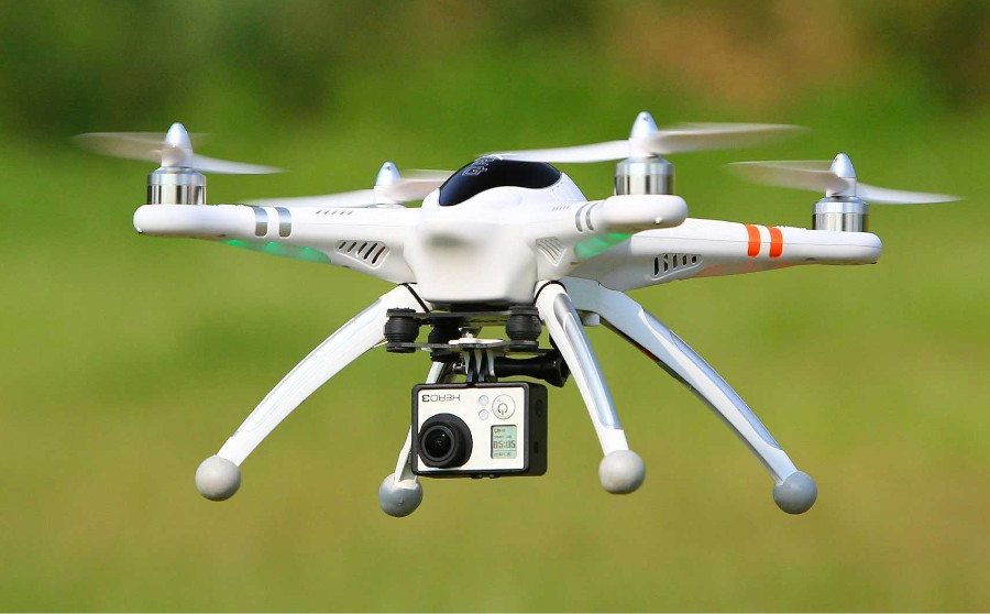 white drone hovering with a camera. Representing Drone cyber security threats