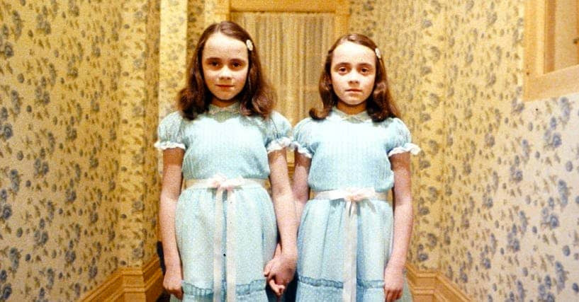 two sinister looking young twin girls from The Shining.
